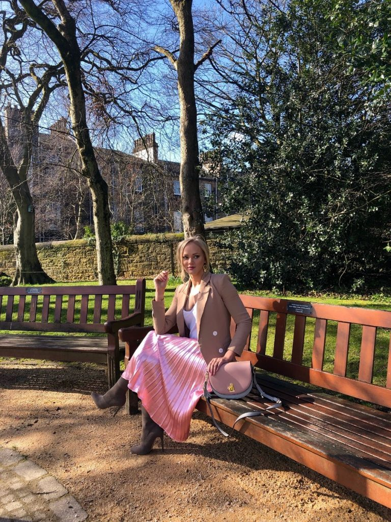 pink satin pleated skirt in a park