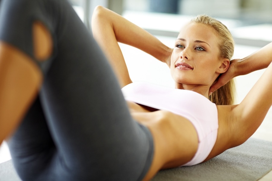 Girl doing sit ups with a smile at home