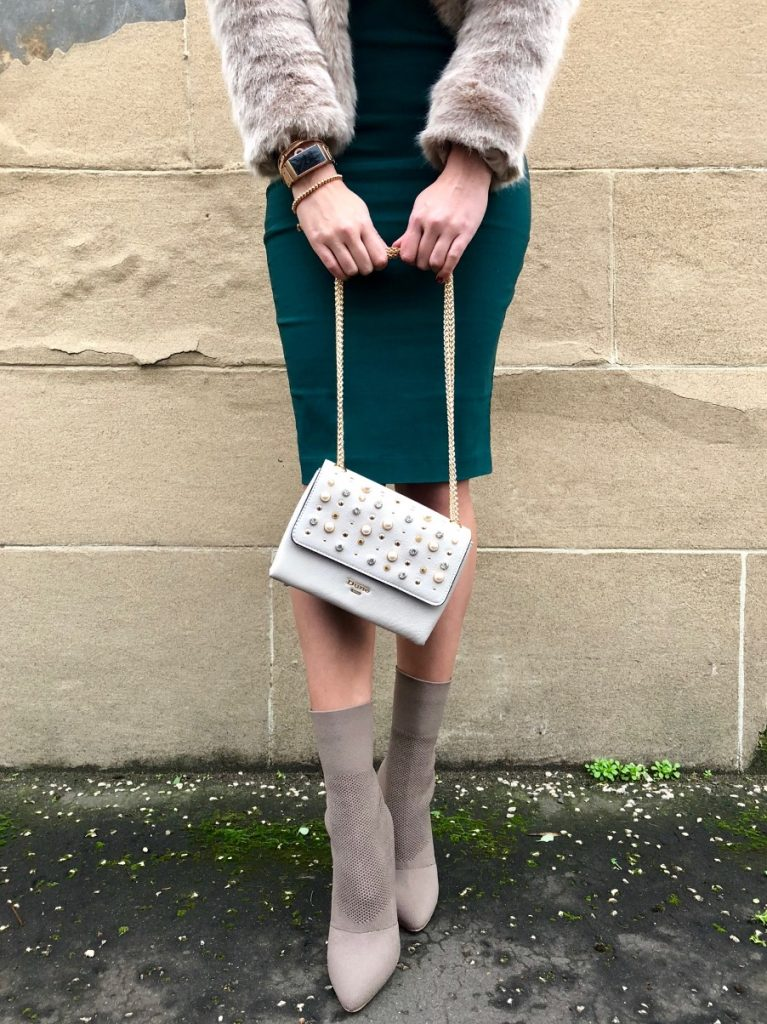 Girl with green skirt and grey sock boots holding a sparkly bag