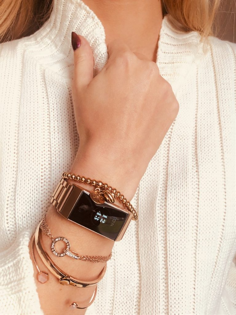 Fitbit fitness tracker on arm with multiple rose gold bracelets
