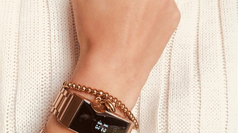 Fitbit on arm with multiple rose gold bracelets