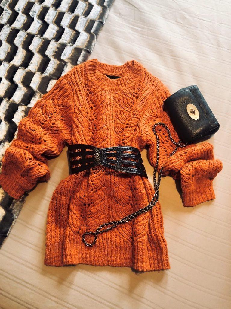 Jewel bright knitted orange jumper flatlay