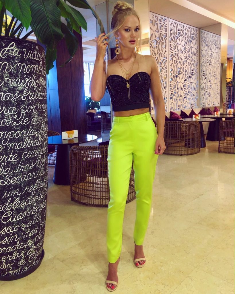 neon green trousers black corset top on vacation