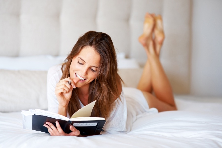 girl on bed relaxing and writing notes of things to do at home