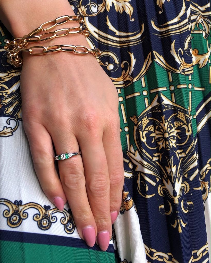 diamond and emerald ring against pleated skirt