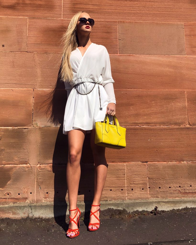 Blonde in white shirt dress and sunglasses