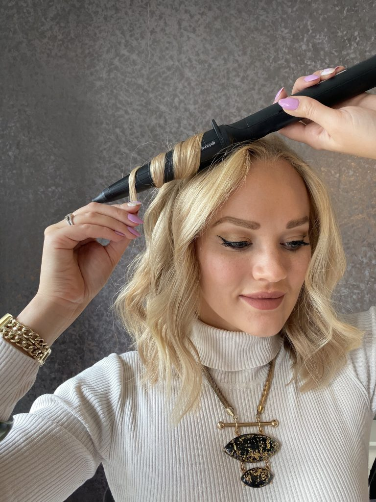 Girl curling hair with GHD Curve Creative Curl Wand