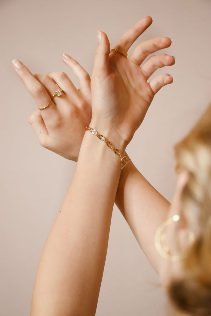 gold bracelet and rings on arm