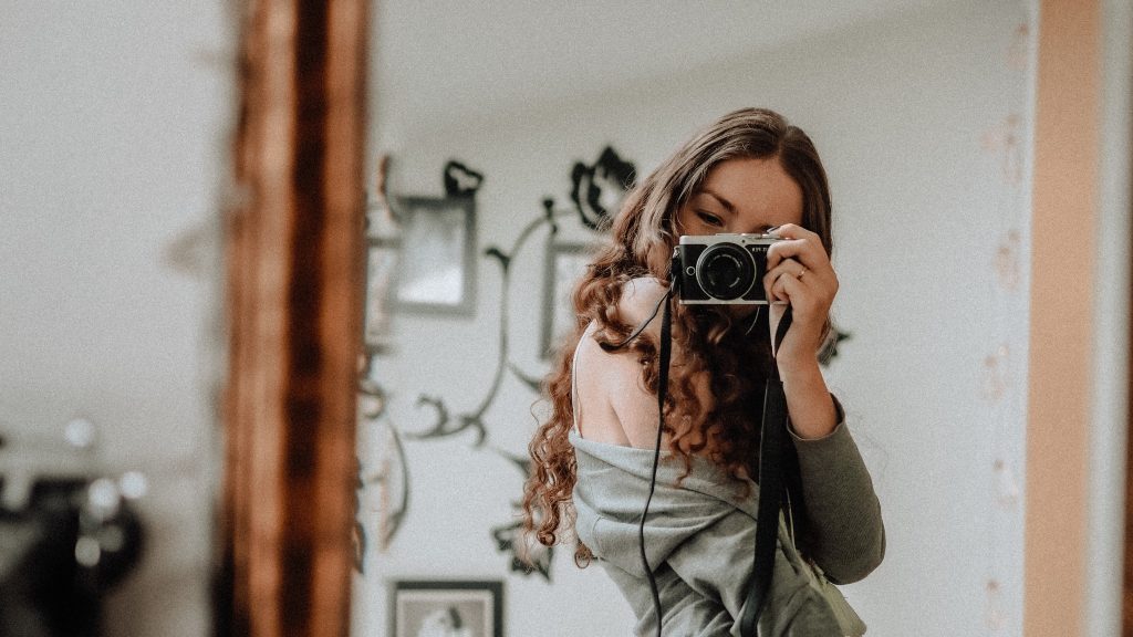 girl taking a selfie with camera to find her style